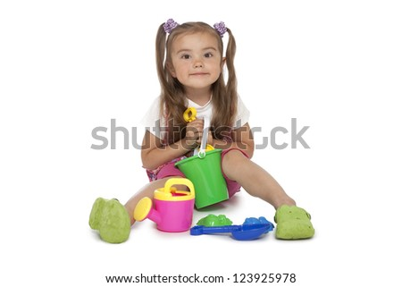 Cute baby girl plays with the toys over white background