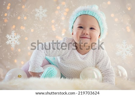 Cute Baby girl posing and smiling with Christmas snowflake ornaments and balls  - stock photo