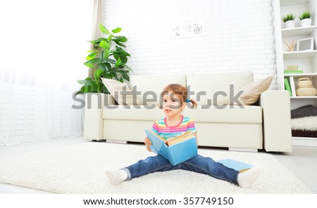 cute baby girl reading a book at home sitting on the floor - stock photo