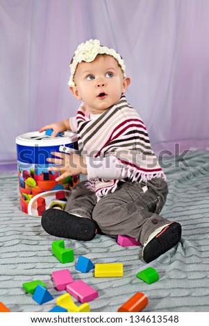 Cute baby girl sitting and playing with developmental toy - stock photo