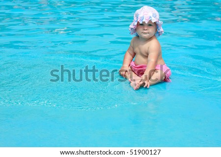 cute baby girl sitting in pool - stock photo