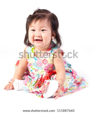 Cute baby girl sitting in studio isolated on white