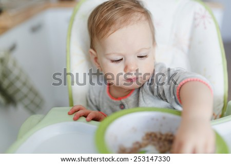 Cute baby girl sitting in the high chair and trying food. baby having her meal  - stock photo