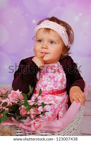 cute baby girl sitting in white wicker basket - stock photo