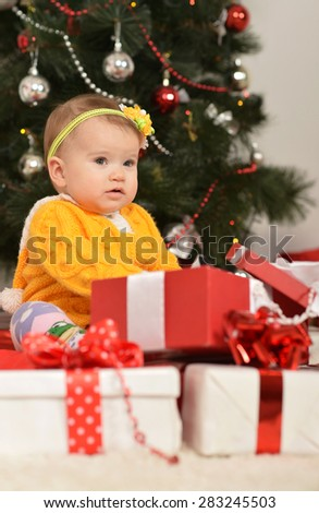 Cute baby girl sitting near Christmas tree with gifts
