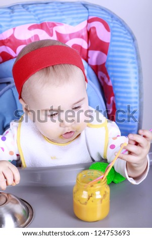 Cute baby girl sitting on high chair and learn to eat