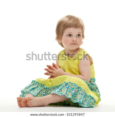 Cute baby girl sitting on the floor; white background