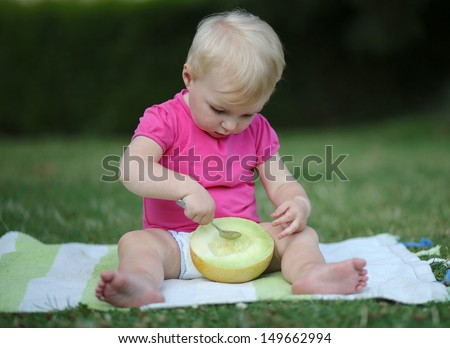 Cute baby girl sitting outdoors on a carpet eating melon with a spoon - stock photo
