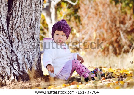 cute  baby girl sitting under the tree