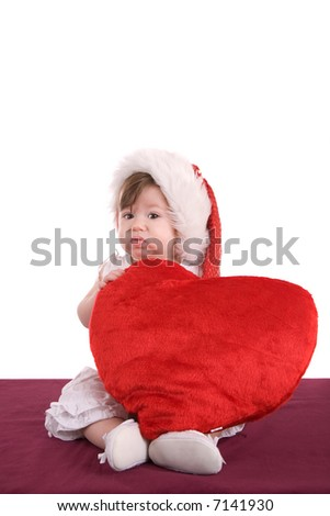 Cute baby girl sitting with a christmas hat and big red heart not looking very happy