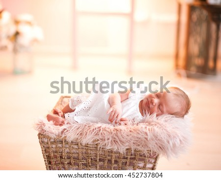 Cute baby girl sleeping in basket on fluffy cover over lights. Childhood. - stock photo