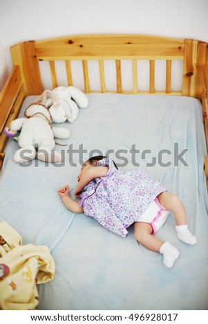 Cute baby girl sleeping in her baby-cot surrounded by some cuddly toys