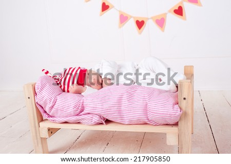 Cute baby girl sleeping in wooden handmade bed with hearts on background. Valentines decorations.  - stock photo