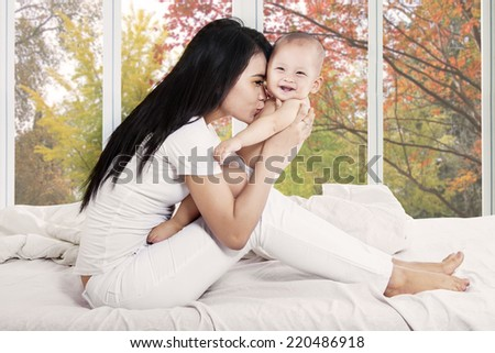 Cute baby girl smiling at camera while mother kiss her body - stock photo