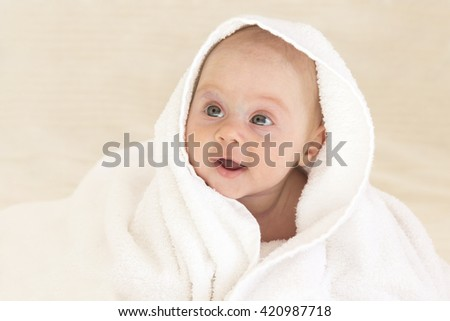 Cute baby girl smiling in a white towel - stock photo