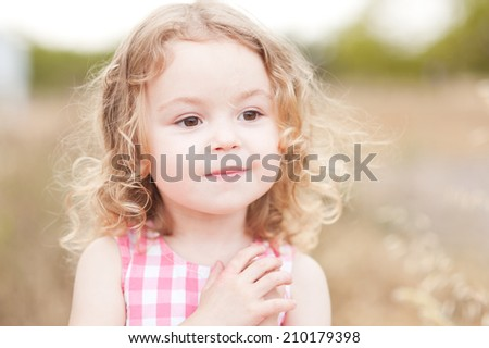 Cute baby girl smiling outdoors on nature background - stock photo