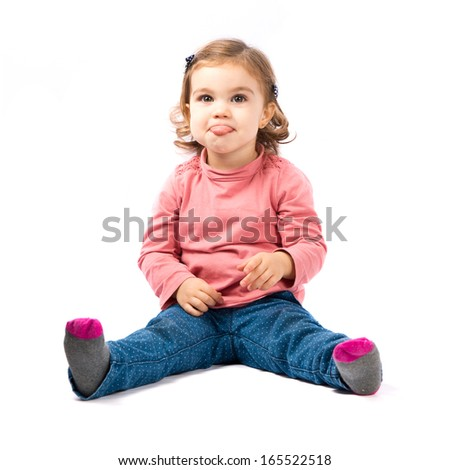Cute baby girl sticking out tongue over white background