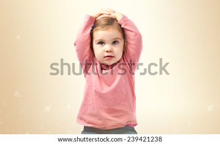 Cute baby girl surprised over ocher background - stock photo