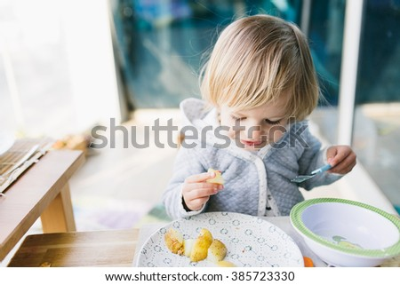 Cute baby girl toddler having lunch eating backed potato on the balcony - stock photo