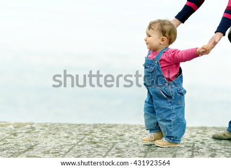 Cute baby girl walking on the promenade by the sea, holding hands mother. Alushta, Crimea. - stock photo