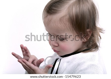 Cute baby girl wearing white cardigan, playfully looking at her hands