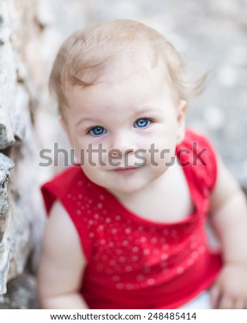 Cute Baby Girl with big blue eyes looking at camera - very shallow depth of field - stock photo