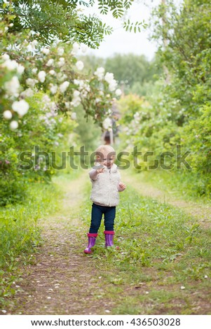 Cute baby girl with blonde hair in the blooming garden outdoors. Little girl 1-2 year old. - stock photo