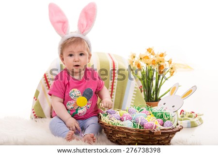 Cute baby girl with fluffy bunny ears and basket with Easter eggs - stock photo