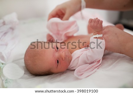 Cute baby girl with hospital ID bracelet getting changed.  - stock photo