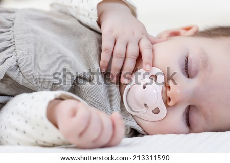 Cute baby girl with pacifier sleeping over white bedcover - stock photo