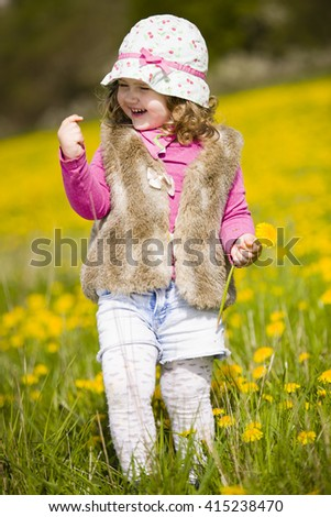 Cute baby girl with sun cap on vivid flower meadow full of yellow flowers. - stock photo