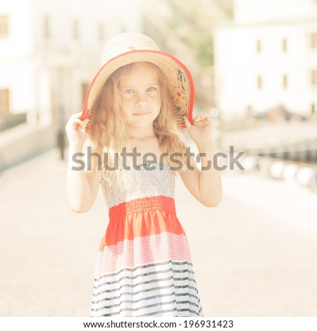 Cute baby girl 5-6 year old walking outdoors. Looking at camera. Wearing stylish summer dress. Childhood.