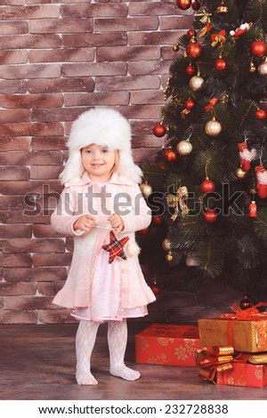 Cute baby girl 5 yeas old playing with christmas decoration over christmas tree in room. Wearing trendy knitted dress, fur winter hat.  - stock photo