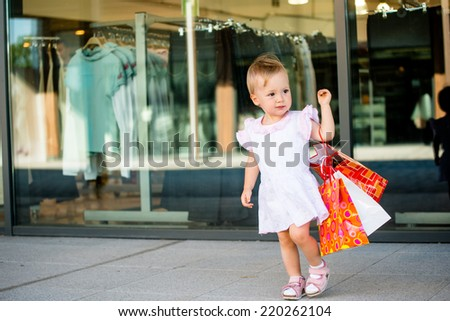 Cute baby goes shopping with bags, shops in background - stock photo