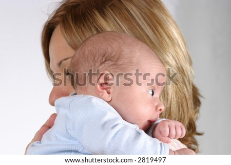 cute baby held by blonde mother on white background - stock photo