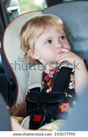 Cute baby his finger in his mouth sitting in the car seat - stock photo