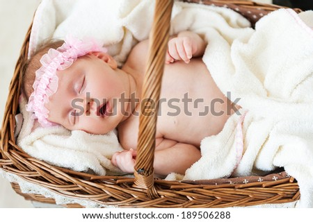 Cute baby in a basket. Top view of little baby sleeping while lying in wicker basket and covered with towel