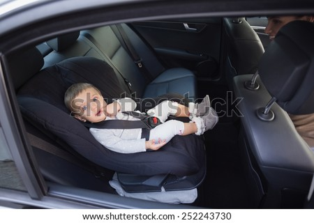 Cute baby in a car seat in the car - stock photo