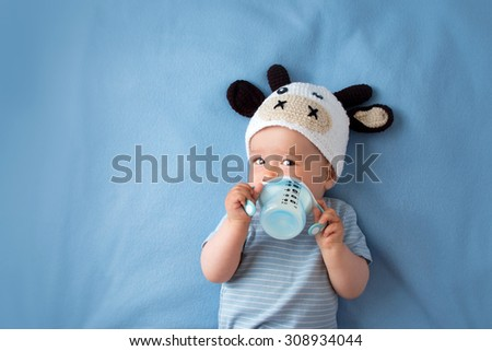cute baby in a cow hat drinking milk - stock photo