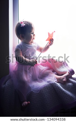 cute baby in a fairy costume sitting on the windowsill and waving a magic wand - stock photo