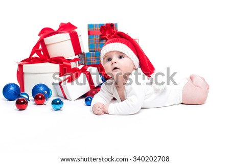 Cute baby in a red New Year's cap with a smile on his face lying on his stomach on a white background surrounded by boxes with gifts.