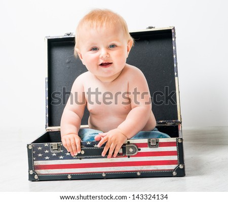 cute baby in a suitcase with American flag - stock photo