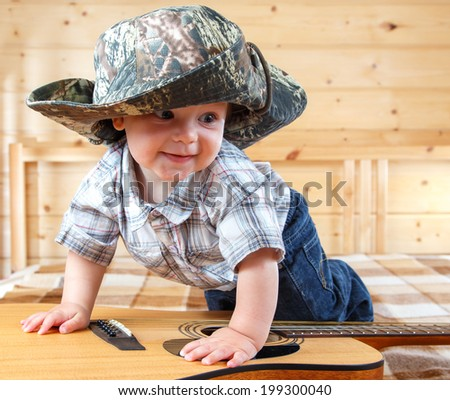 Cute baby in cowboy hat climbing the guitar - stock photo