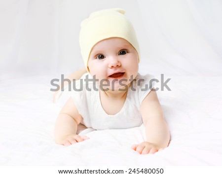 Cute baby in hat on the bed at home - stock photo