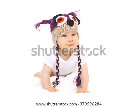 Cute baby in knitted hat crawls on a white background - stock photo