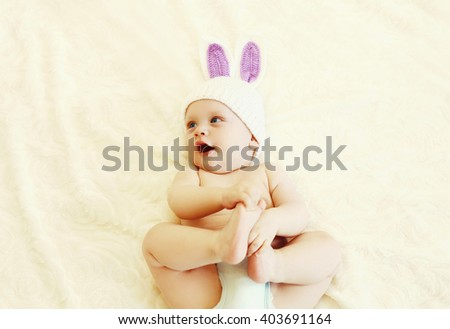 Cute baby in knitted hat with a rabbit ears lying on bed at home - stock photo