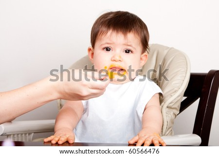 Cute baby infant boy girl expresses dislike disgust for food fed by spoon.