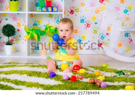 Cute baby is playing with toys at home - stock photo