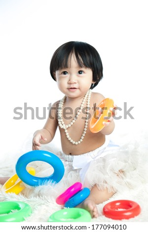 Cute baby is playing with toys over white background, wearing a white necklace - stock photo