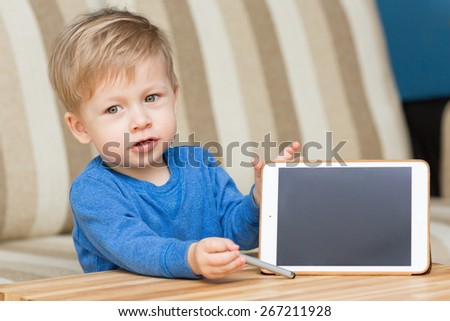 Cute baby, kid with tablet pc, showing the screen of tablet pc.